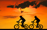 Silhouette group friend  and bike relaxing on blurry sunset background.