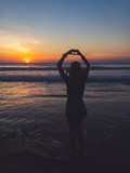 Girl making heart - shape sign with hands on the sea / ocean sunset.