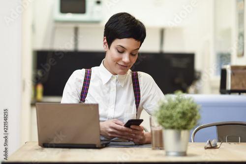 Young businesswoman with very short haircut looking at her smartphone at home.