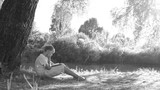 Portrait of young cute caucasian kid reading book outside sitting on ground under old tree in summer sunset light. Black and white 4k video footage. - 221563044