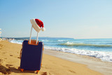Santa Claus hat on a suitcase on the beach by the sea. Christmas on vacation by the sea. Concept of Christmas in a summer resort.