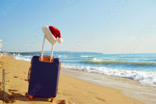 Santa Claus hat on a suitcase on the beach by the sea. Christmas on vacation by the sea. Concept of Christmas in a summer resort. - 221566046