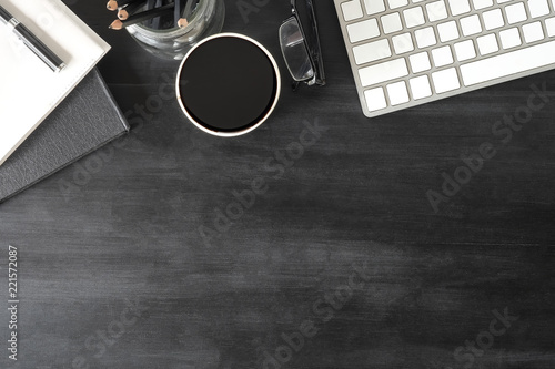 Biurka komputerowa klawiatura, notatnik, pióro i kawa na czarnym stole.