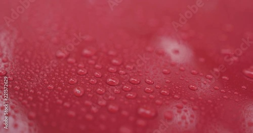handheld shot of water drops on red car with hydrophobic coating