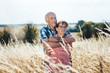 Leinwandbild Motiv Senior Mann kuschelt mit seiner Frau auf der Wiese im Gras