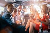 Gruppe von Männern und Frauen macht Party in Limo und trinkt Sekt