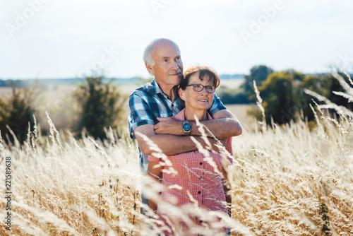 Leinwanddruck Bild Senior Mann kuschelt mit seiner Frau auf der Wiese im Gras