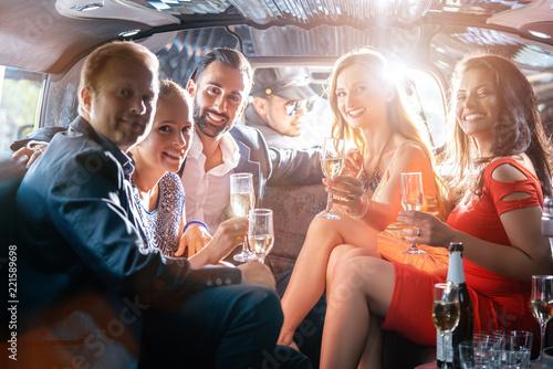 Gruppe von Männern und Frauen macht Party in Limo und trinkt Sekt - 221589698