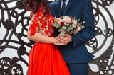 Close up of bride in red wedding dress, bridegroom and bridal bouquet - 221589867
