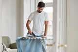 Hard working young Caucasian bearded husband irones clothes on ironing board, does domestic duties while wife is away, stands in living room, being busy with work about house. Chores concept - 221592001