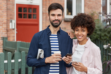 Outdoor shot of multiethnic couple stand closely to each other against brick building background, being always in touch, use modern cellulars, drink takeaway coffee, have positive expressions