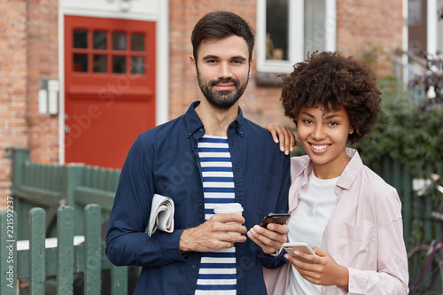Outdoor shot of multiethnic couple stand closely to each other against brick building background, being always in touch, use modern cellulars, drink takeaway coffee, have positive expressions - 221592237