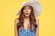 Emotive surprised fashionable woman in summer hat, stares with bugged eyes, opens mouth from surprisement, dressed in polka dot clothes, stands against yellow background. Surprisement concept