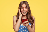 Cheerful positive woman holds modern cell phone, forgets telephone number of boyfriend, plays apps, communicates in social networks, has happy expression dressed in polka dot dress, isolated on yellow - 221592840