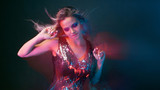 Bright and stylish young woman dancing in club, color light, motion effects - 221595060