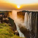 Victoria falls sunset with orange sun and tourists - 221595075