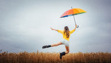 Frau freut sich über den Regen und springt mit dem Regenschirm in die Luft - 221597688
