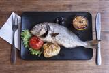 Dorado fish on a black plate - 221602656