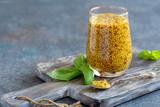 Mustard sauce in a glass jar and fresh basil. - 221603614