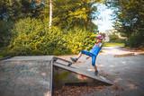 Ein Mädchen stürzt beim Skateboard fahren auf einer Rampe