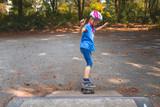 Ein Mädchen skatet mit dem Longboard auf einem Skatepark auf eine Rampe