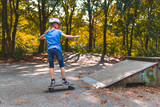 Ein Mädchen skatet mit dem Longboard auf einem Skatepark auf eine Rampe zu
