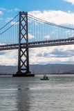 bay bridge and a boat in san francisco, view of the bay bridge in san francisco and a boat passing below it during morning.