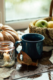 Autumn, window, tea mug and raindrops, fallen leaves, coziness, apples in a basket and pumpkin - 221617823