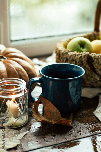 Autumn, window, tea mug and raindrops, fallen leaves, coziness, apples in a basket and pumpkin