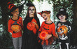 Leinwandbild Motiv happy Halloween! a group of children in suits and with pumpkins in forest