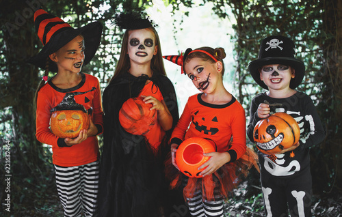 Leinwanddruck Bild happy Halloween! a group of children in suits and with pumpkins in forest