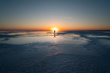 Beautiful sunset on the salt lake El'ton. Small silhouette of a woman standing with hands up straight in front of setting sun.