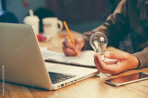 Naklejka business man accountant holding light bulb, new idea with innovation concept