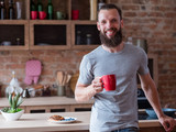 traditional quick breakfast of tea and pastry. food and eating habits concept. smiling happy bearded man holding a red mug standing in the kitchen. - 221647271