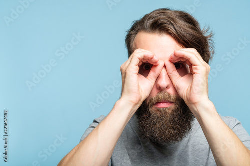 Leinwanddruck Bild funny ludicrous joyful comic playful man pretending to look through binoculars made of hands. portrait of a young bearded guy on blue background. emotion facial expression concept