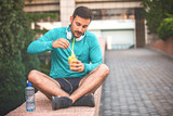 Man is eating fruit after morning workout - 221649631