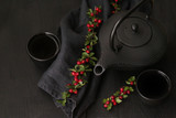 Autumn tea mood. black teapot in Asian style, black linen napkin with berry branches on a black wooden background.tea ceremony in a minimalist style - 221653029