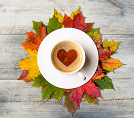 Fall in love. Coffee cup with heart symbol on autumn colorful leaves on wooden table, top view