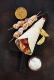 Black wooden serving board with chicken souvlaki in tortilla wrap. Flatlay on a dark brown metal background, studio shot - 221658808