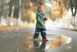 cheerful little girl walks and jumps in puddles in the rain - 221664811