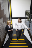 Young business people climbing up stairs in modern office - 221668211