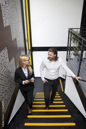 Młodzi ludzie biznesu wspina się w górę schodków w nowożytnym biurze
