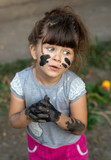 Sorry, please! Funny kid, dirty face. Happy pretty kid girl playing outside with dirty hands.  Messy. - 221676627