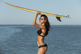 Gorgeous dark-haired girl in a black swimsuit and sunglasses holds a yellow surfboard over her head near the sea on a sunny day. - 221687431