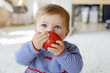 Leinwanddruck Bild - Little adorable baby girl eating big red apple. Vitamin and healthy food for small children. Portrait of beautiful child of 6 months