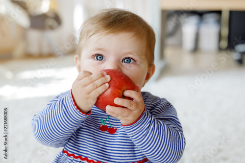 Leinwanddruck Bild Little adorable baby girl eating big red apple. Vitamin and healthy food for small children. Portrait of beautiful child of 6 months