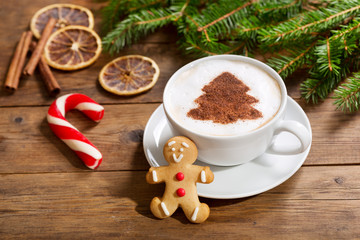 Cup of cappuccino coffee with christmas tree drawing and gingerbread cookie