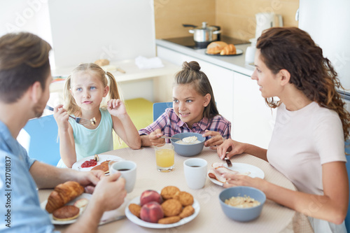 Young parents discussing where to spend following weekend during breakfast in the kitchen - 221701837