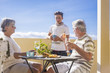 grandfathers adult mature and teenager nephew enjoy outdoor in the terrace some leisure with food and drinks. ocean and city view, vacation sunny day nice weather concept and background. happy people
