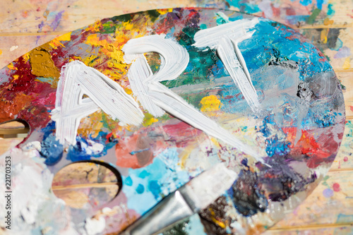 Leinwanddruck Bild Word art painted with white gouache on colorful palette with paintbrush near by